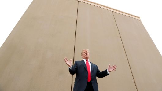 President Donald Trump stands in front of a border wall prototype.