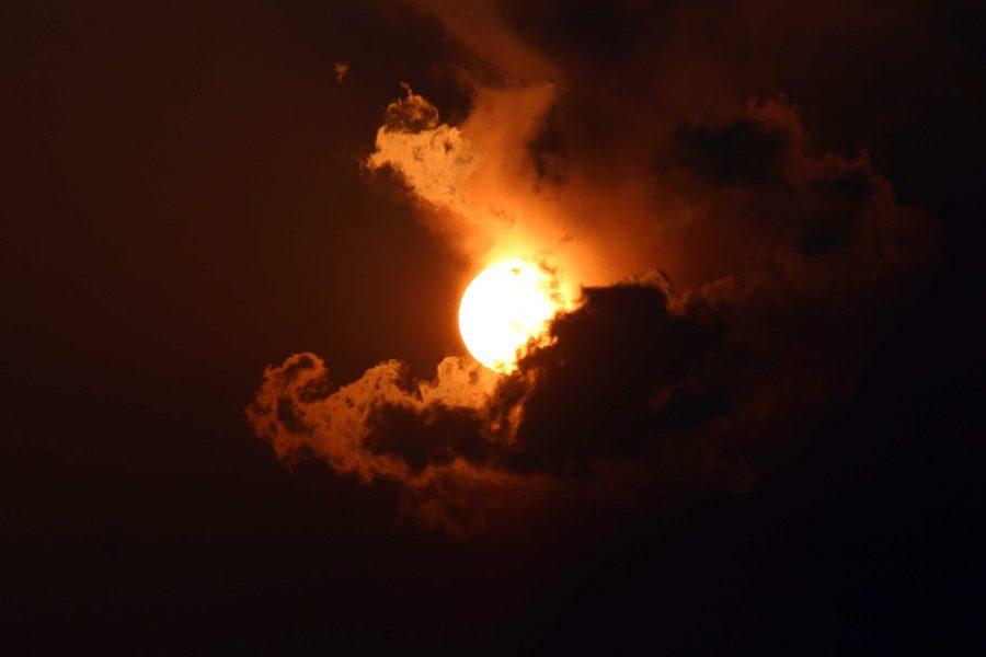 Sun behind dark clouds