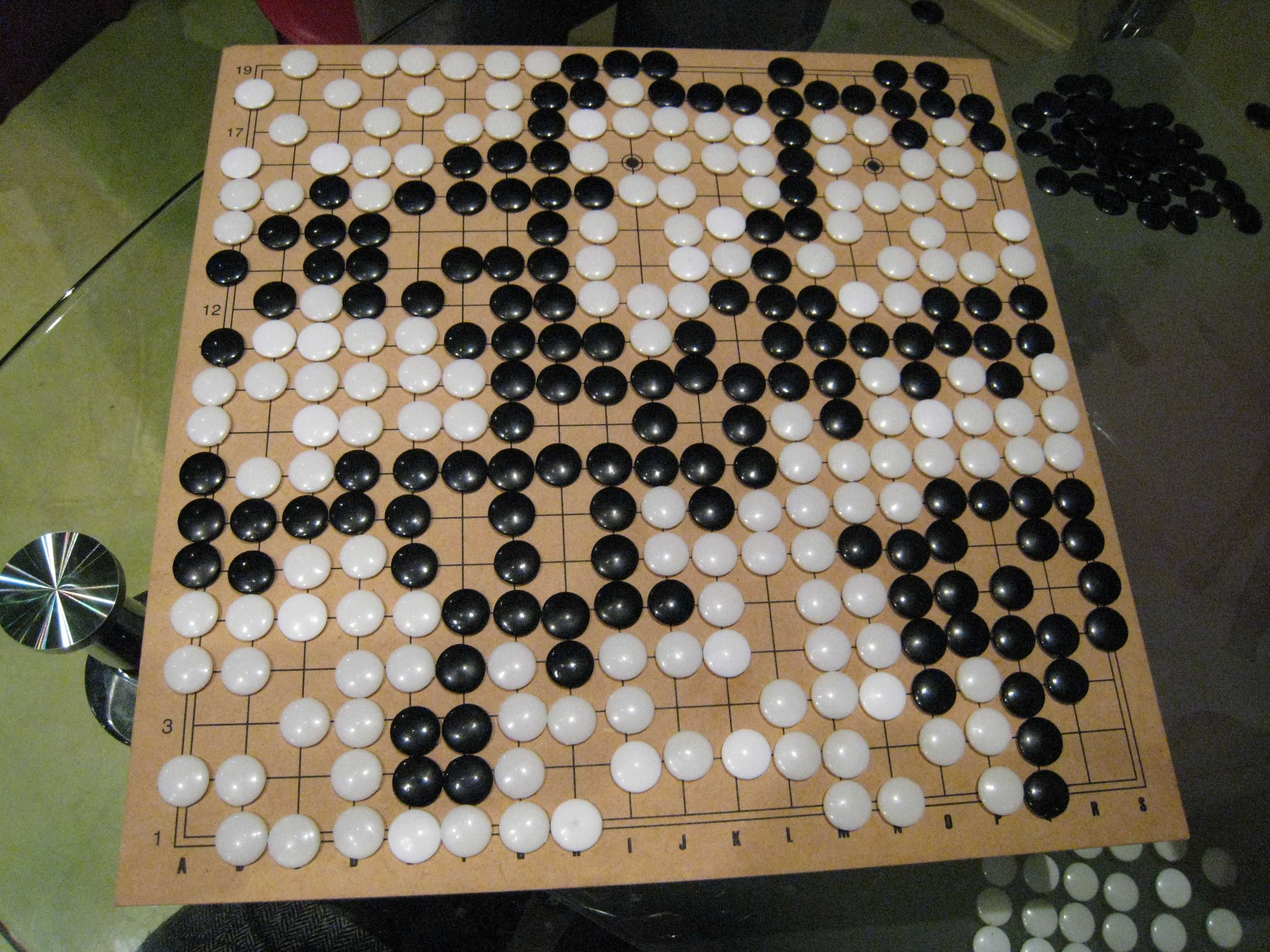 The board for the game Go, with circular black and white pieces on a grid