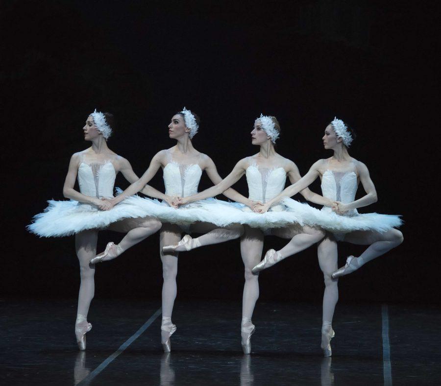 4 dancers in white, swan-like tutus, all balanced on one leg