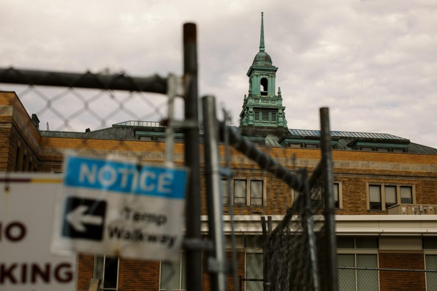 Simmons cupola and main college building obstructed by construction fencing.